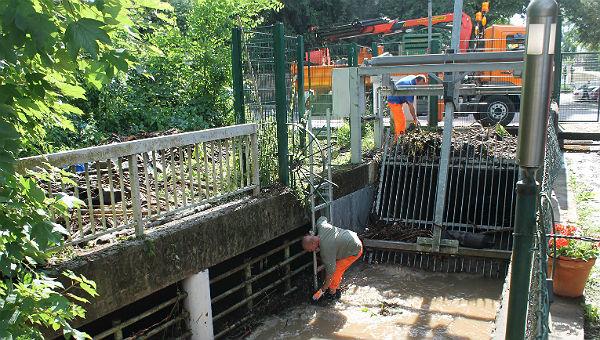 Städtische Mitarbeiter überprüfen den Rechen am Strundekanal