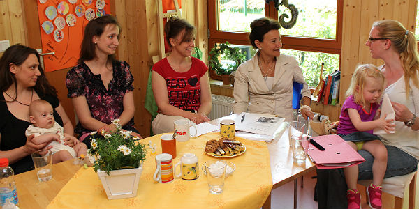 Simone Spinath (Tagesmutter), Silke Geißler (Leiterin des Familienzentrums) und Mareike Boljahn (Stadtjugendamt) beim Beratungsgespräch mit zwei jungen Müttern.