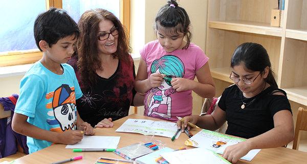 Flüchtlingskinder mit der Lehrerin Mimoza Leka