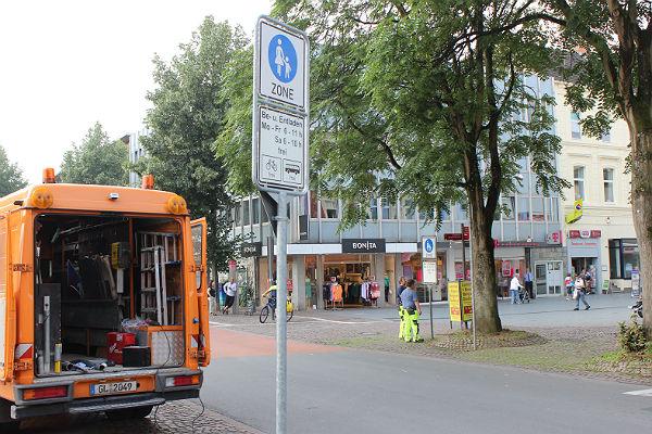 Bauhof-Mitarbeiter kürzen Schilder in Bergisch Gladbachs Fußgängerzone