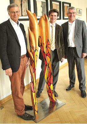 """Wolfgang Bosbach, Roman Salyutov und Lutz Urbach mit dem Erkennungszeichen der Festwoche, die Skulptur von Georg Becker """"Langsam wächst zusammen, was zusammengehört'"""