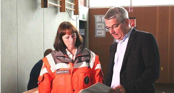 Bürgermeister Lutz Urbach informiert sich in der Halle bei DRK-Teamleiterin Schmidt