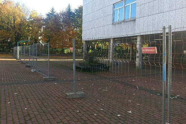 Der Schulhof des Berufkollegs ist mit einem Zaun abgetrennt. Ein Tor führt hindurch