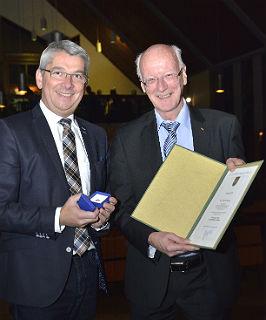 Bürgermeister Lutz Urbach verleiht Heywang die Ehrennadel. Foto: Anton Luhr