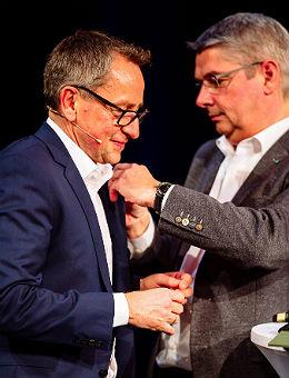 Urbach steckt Linzenich die Ehrennadel an. Foto: Photographie Andreas Weinand
