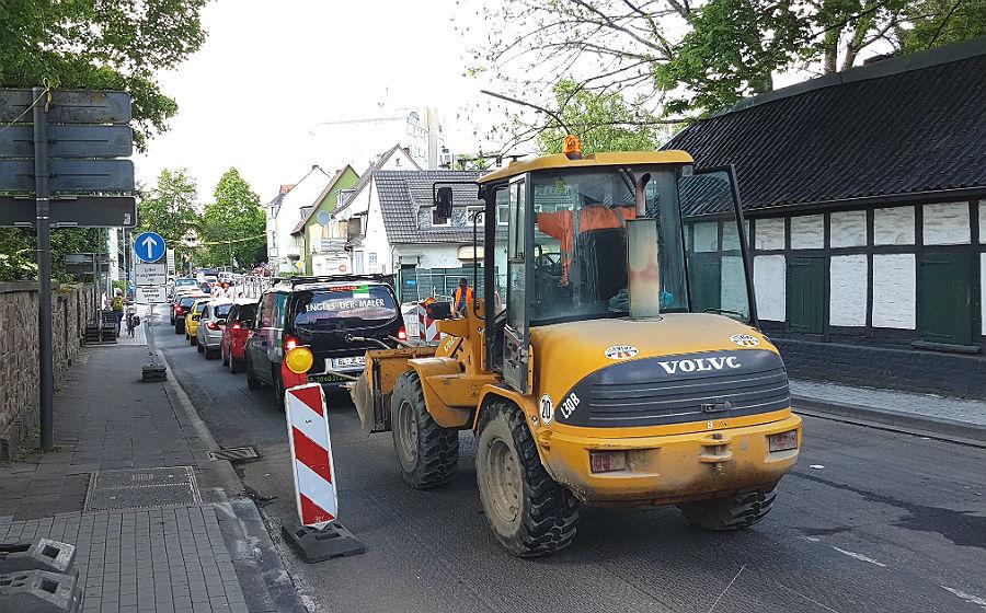 Unter Hochdruck und noch mitten im Verkehr wird die Odenthaler Straße für die Asphaltierung vorbereitet