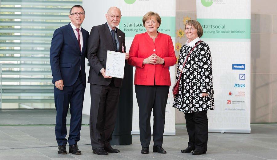 Angela Merkel mit start-social-Chef Dieter Düsedau und den MiKibU-Vertretern Christiane Müller und Henry Stewen