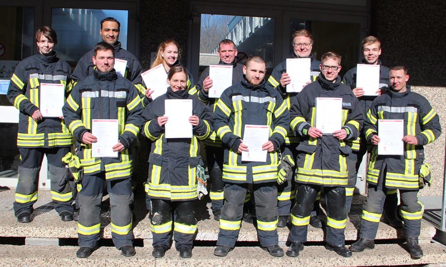 Einige der 38 Absolventinnen und Absolventen der Grundausbildung mit ihren Urkunden.