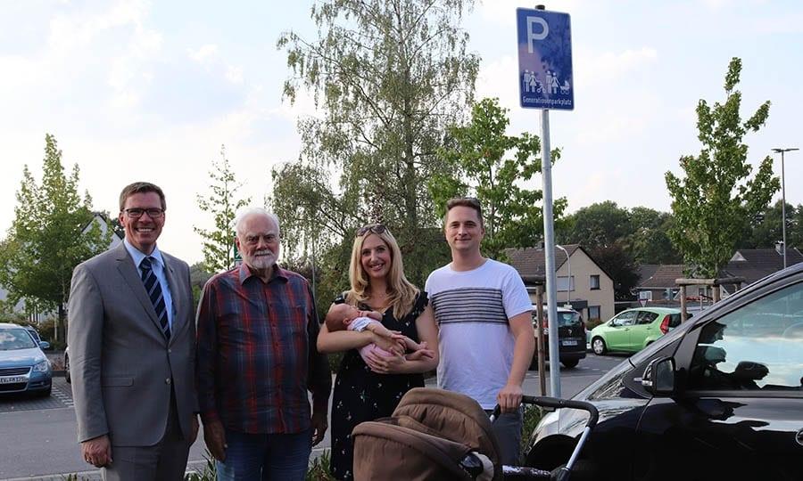 Landrat Stephan Santelmann, Rudolf Preuß, der Vorsitzende des Kreis-Seniorenbeirats, Sarah Fischer, ihr Mann Marco und Töchterchen Emilia vor den Generationenparkplätzen.